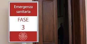 cartello con dicitura su sfondo rosso e portone marrone aperto chiosco uniss